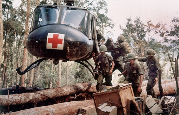 American 4th Battalion, 173rd Airborne Brigade soldiers loading wounded onto an UH-1D Huey helicopter being evacuated from Hill 875 15 miles southwest of Dak To during the Vietnam War.
