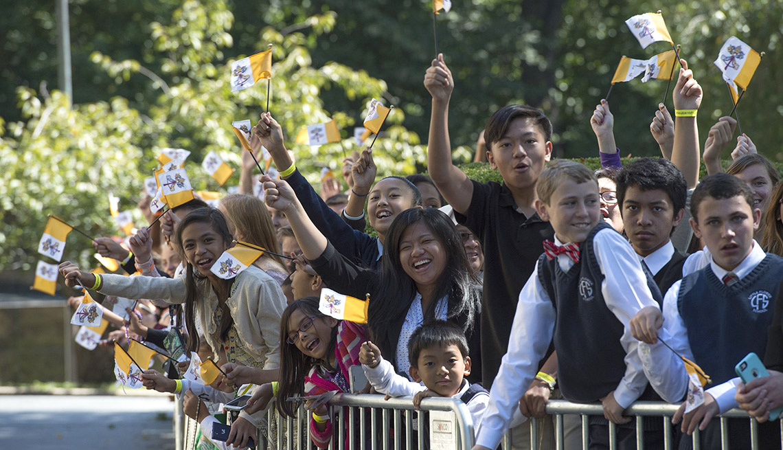 School children and parents cheer while waiting for Pope Francis to return at the Apostolic Nunciature to the United States on September 23, 2015 in Washington, DC.