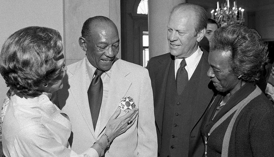 First lady Betty Ford admires Jesse Owens' Medal of Freedom during a White House reception