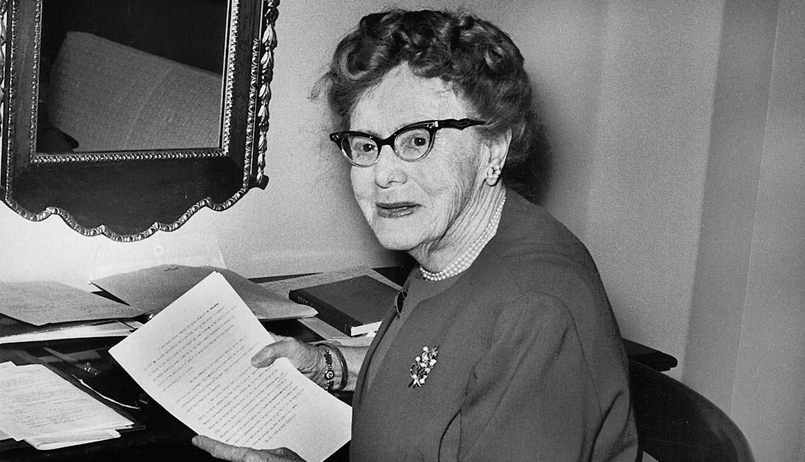 Ethel Percy Andrus sentada mientras sostienen un documento en las manos.