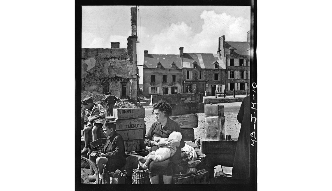 After D-Day, 'Somewhere in France' - Refugees pause in Montebourg, a town in Normandy, on July 24. The cases hold U.S. food rations from the Raritan Arsenal in Metuchen, N.J.