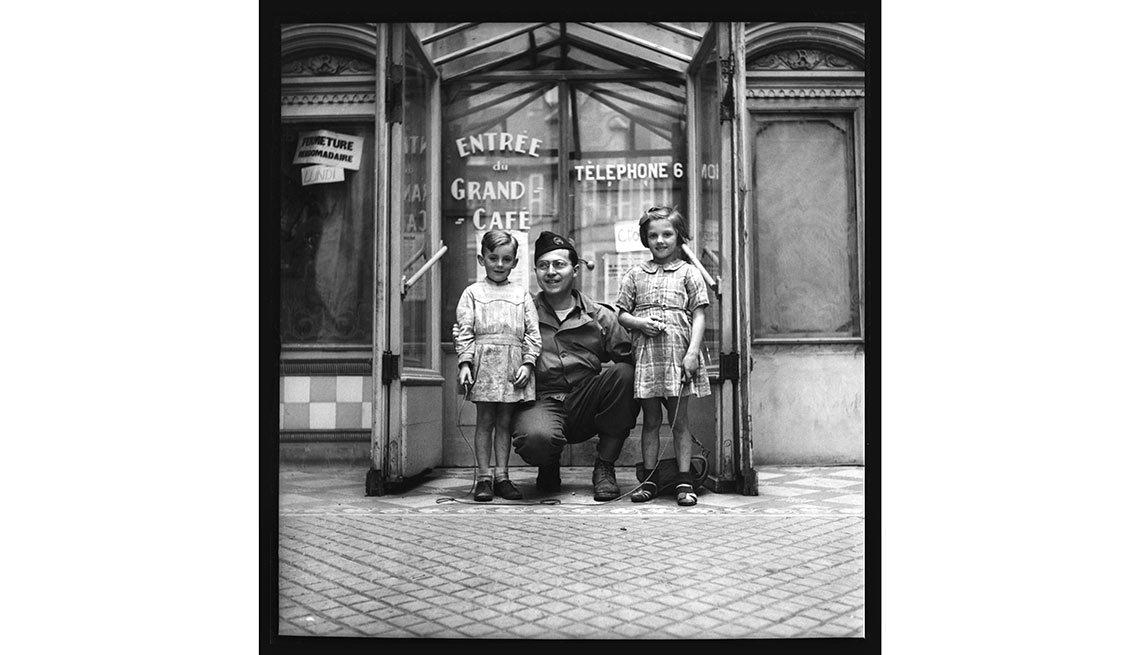 El fotógrafo John Morris se sitúa frente a la cámara y posa con dos niños franceses