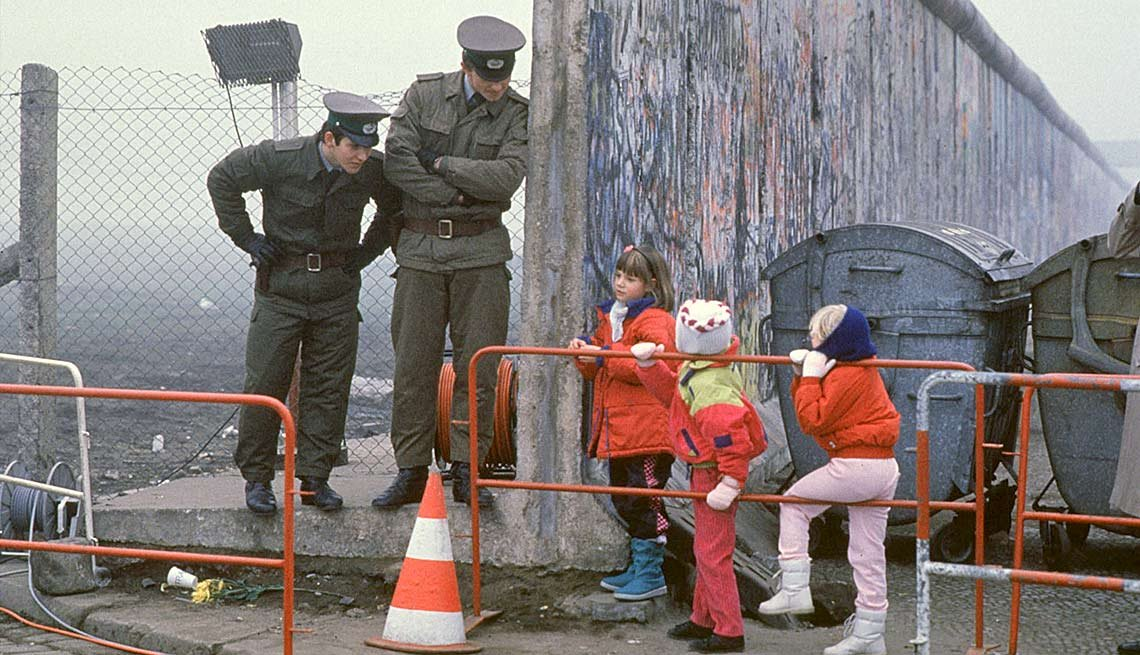 Militares conversan con unos niños a través del muro de Berlín