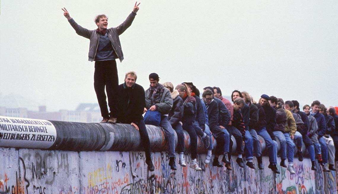 Man standing on Berlin Wall, 1989, 25th anniversary, Fall of the Berlin Wall