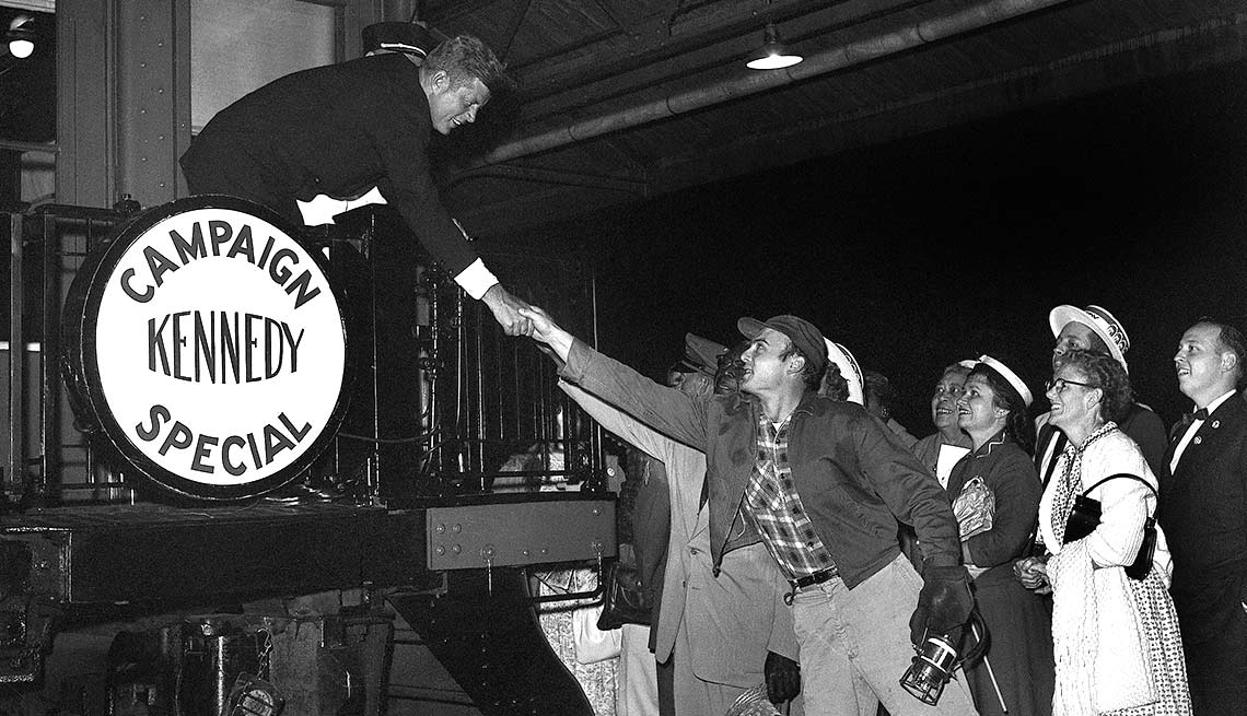 Kennedy shakes the hand of a well wisher shortly after boarding a train for a whistle-stop tour of California.