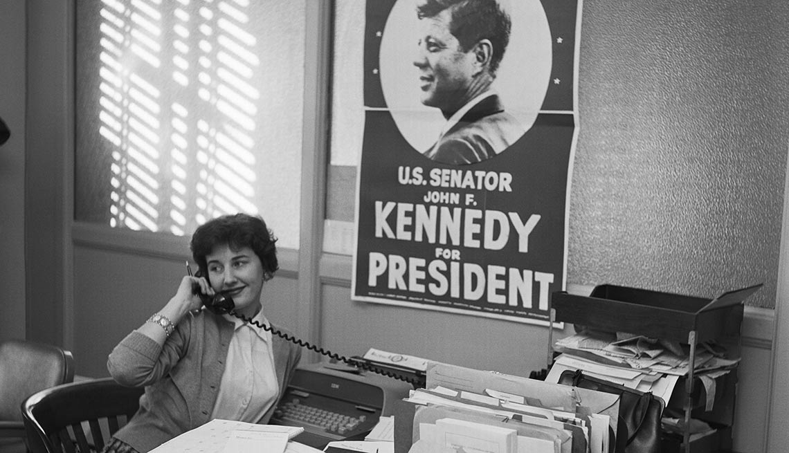A campaign staffer from Miami works beneath an image of her candidate.