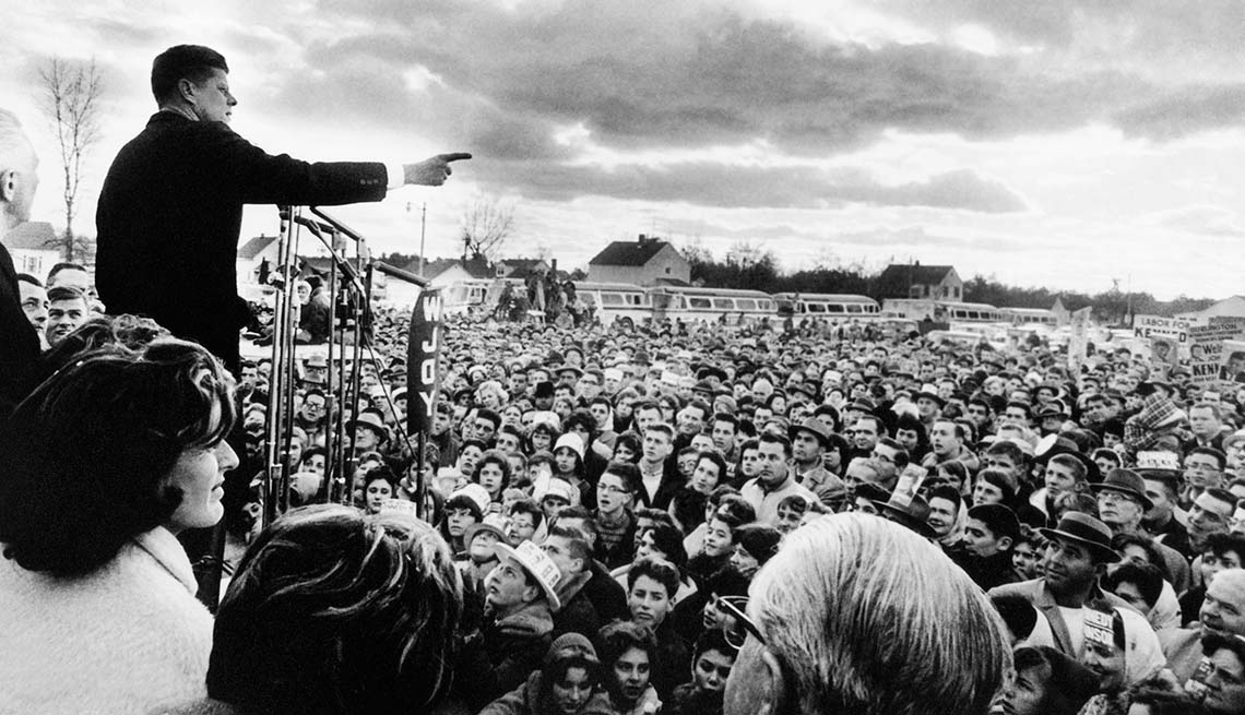 Senator and Democratic presidential nominee, John F. Kennedy, delivers a campaign speech to a large crowd outside.