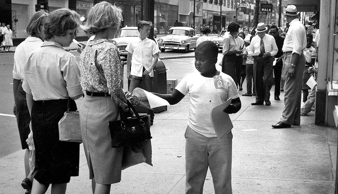 Niño negro entrega un boletín informativo a unos transeúntes - 1963