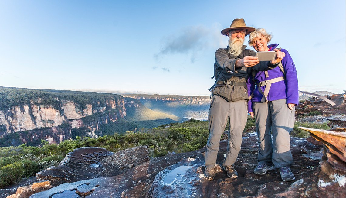 Pareja de adultos mayores tomándose un selfie en un lugar remoto