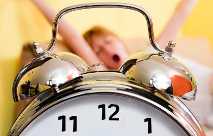 Reloj en primer plano y mujer bostezando al fondo