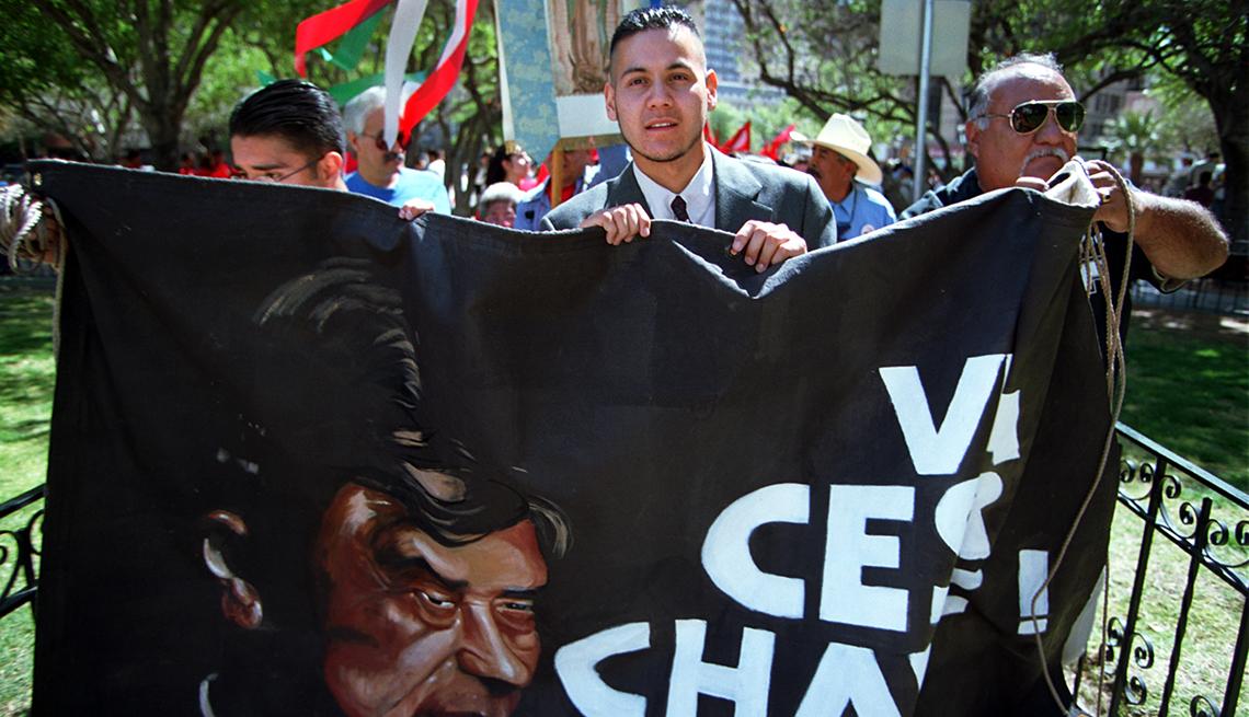 item 12 of Gallery image - Ricardo Chávez, de 26 años, sobrino de César Chávez, sostiene una pancarta con la imagen de su tío
