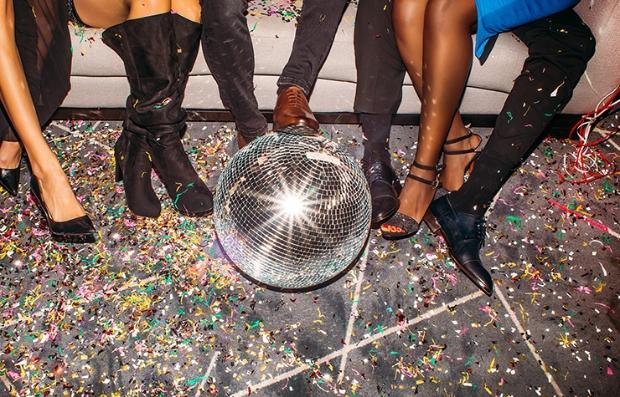 Imagen de una bola de espejos en el suelo y pies de varias personas sentadas para recordar las fiestas estilo disco.