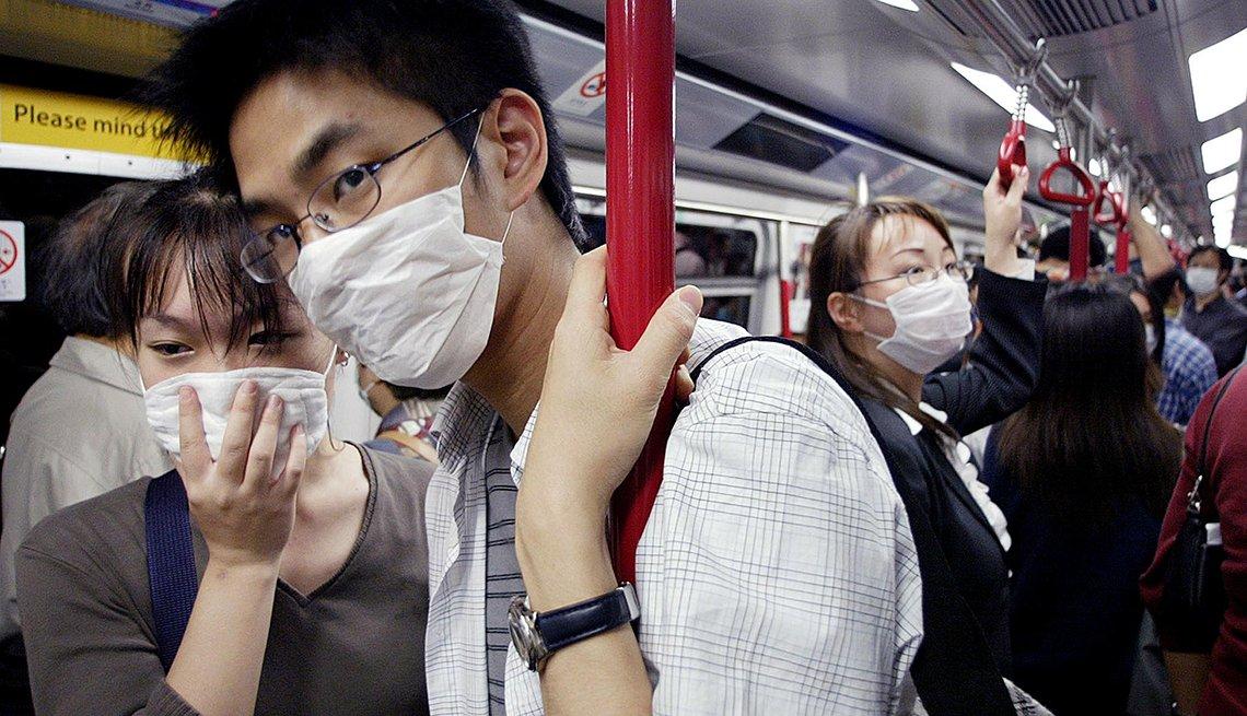 Personas en el metro utilizando máscaras para protegerse contra infecciones