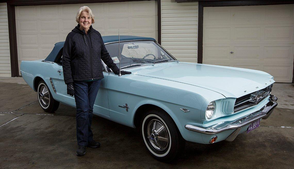 Gail Wise posa con su Ford Mustang convertible de color azul cielo frente a su garaje, donde se sentó durante 27 años antes de su restauración, en Park Ridge, Illinois