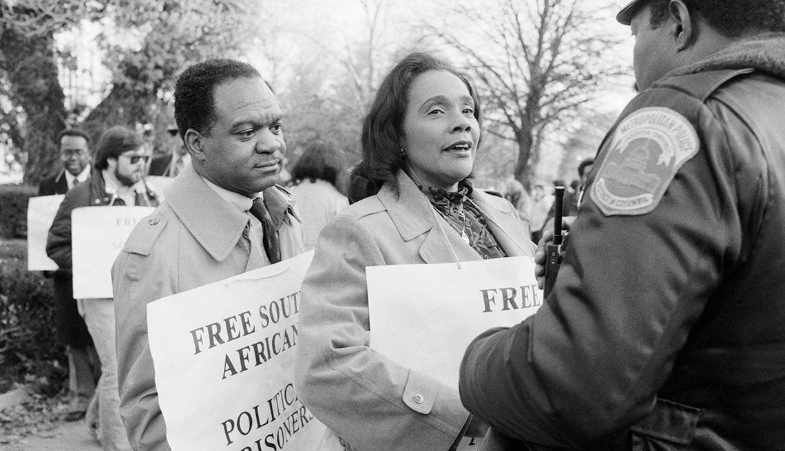 Coretta Scott King y delegado Walter Fauntroy de Washington, DC hablan con un oficial de policía de DC mientras protestaban frente a la embajada de Sudáfrica en 1984.