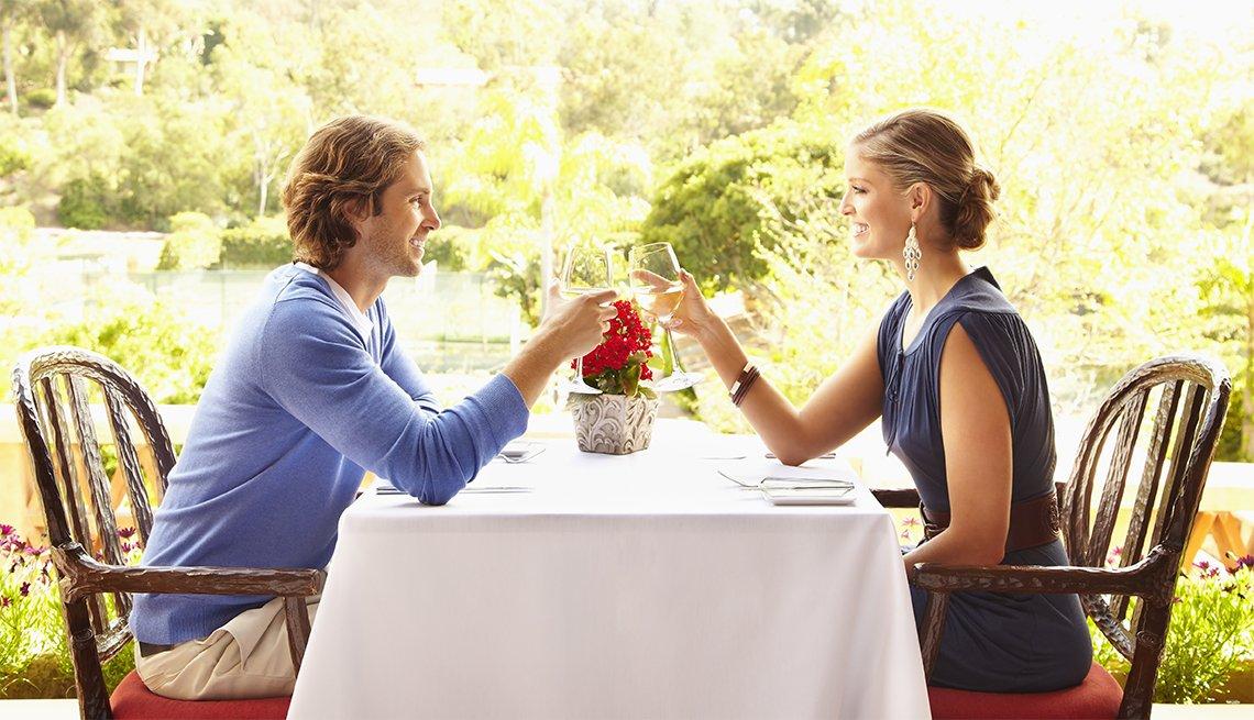 Pareja joven, caucásica, disfrutando de una cena al aire libre