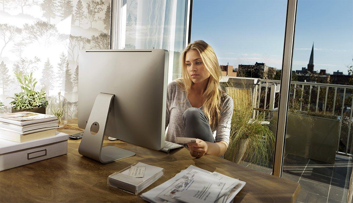 Joven mujer mirando su computadora y sosteniendo tarjeta en su mano
