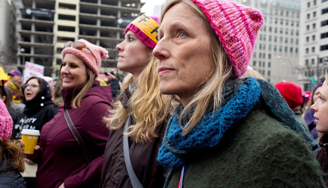woman protestor with pink hat in street with other women