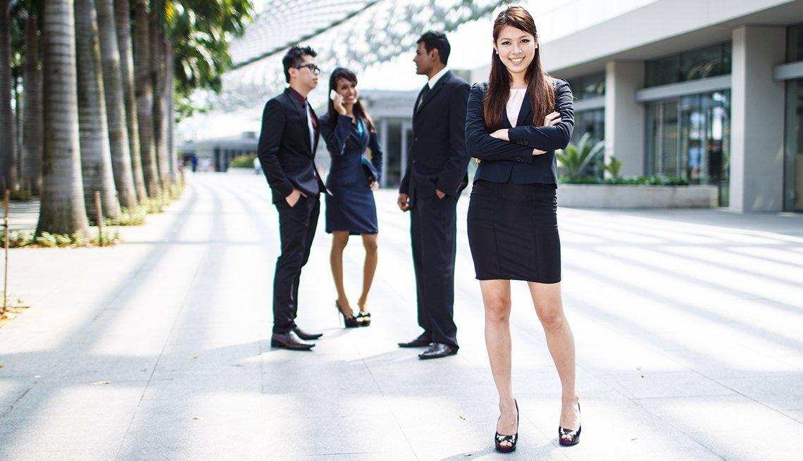 Mujer hispana vestida en traje de oficina, con otras personas detrás con trajes de negocios