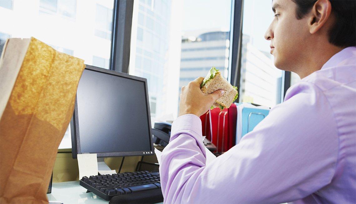 Hombre joven sentado en su oficina frente a un computador comiéndose un sándwich