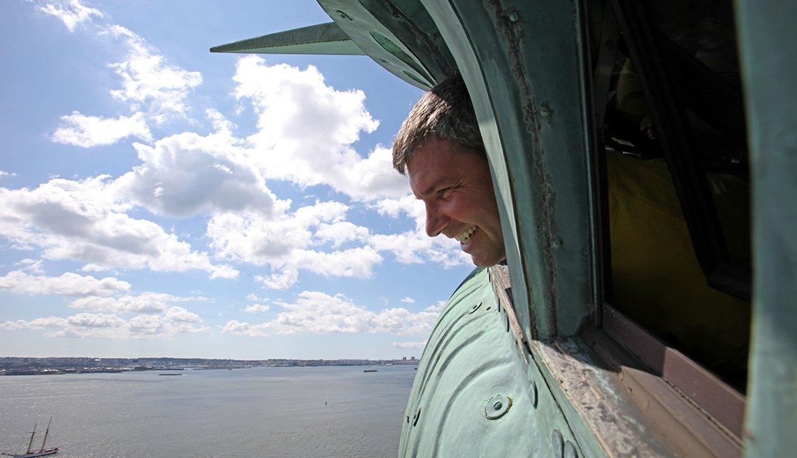 Turista asoma su cara sonriendo desde la corona de la Estatua de la Libertad