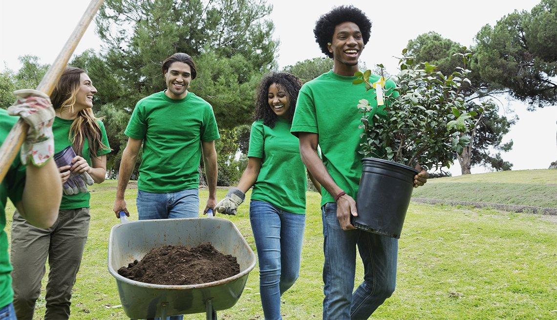 Un grupo de jovenes voluntarios de diferentes razas étnicas con plantas y una carretilla llena de tierra