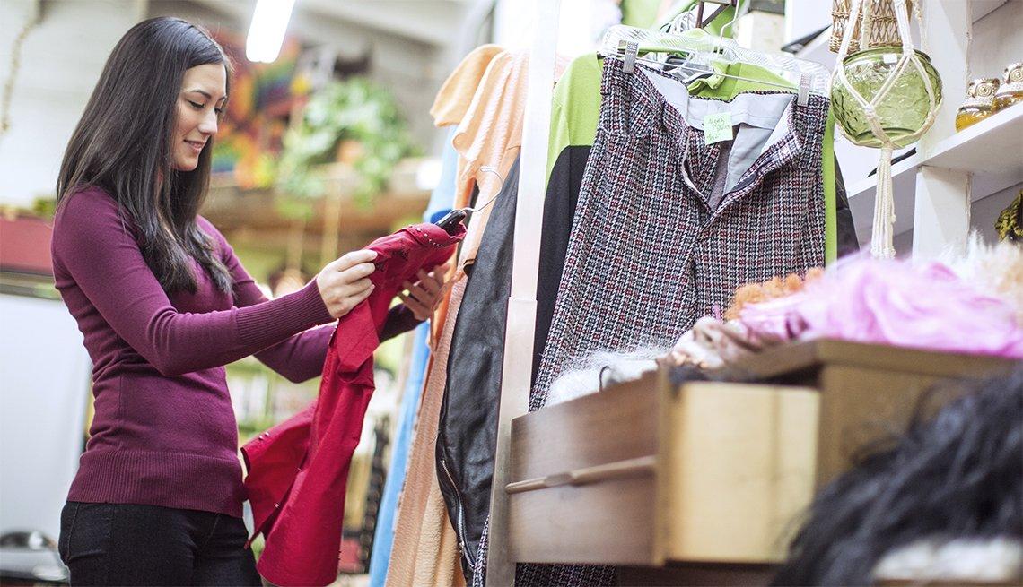 Joven mujer mirando un vestido rojo dentro de una tienda