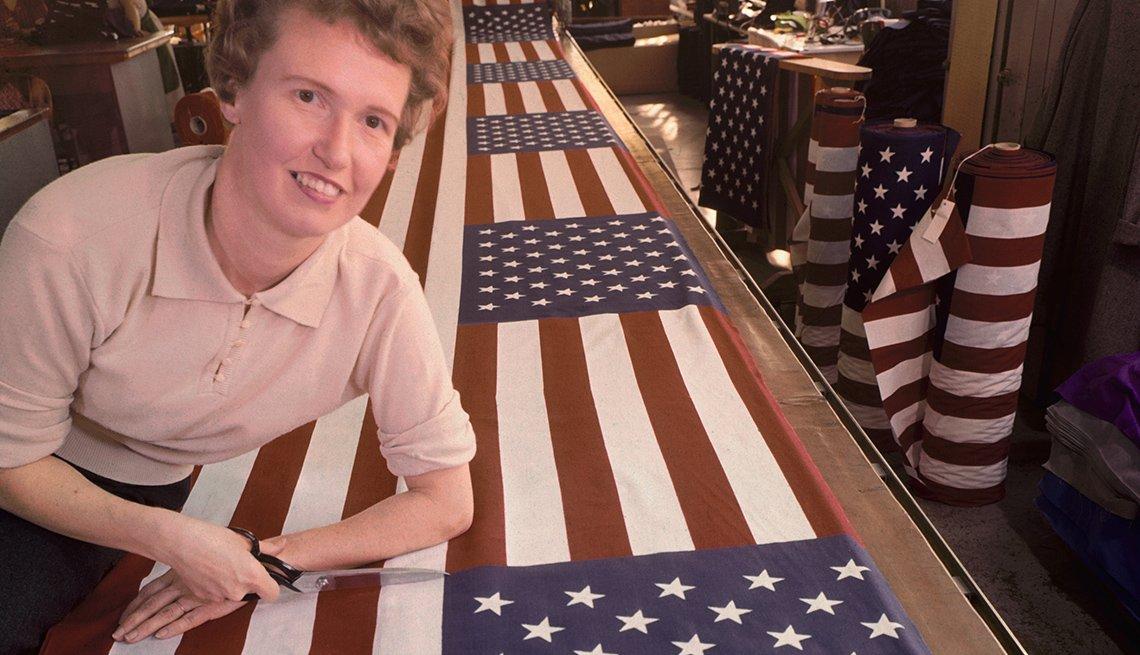Mujer trabajadora de una fábrica inspeccionando una bandera americana
