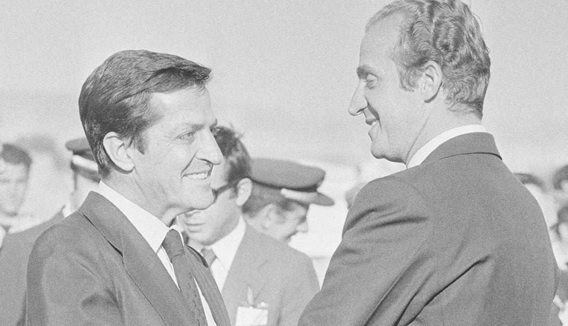 Foto a blanco y negro del rey de España Juan Carlos y Adolfo Suarez saludandose amablemente.