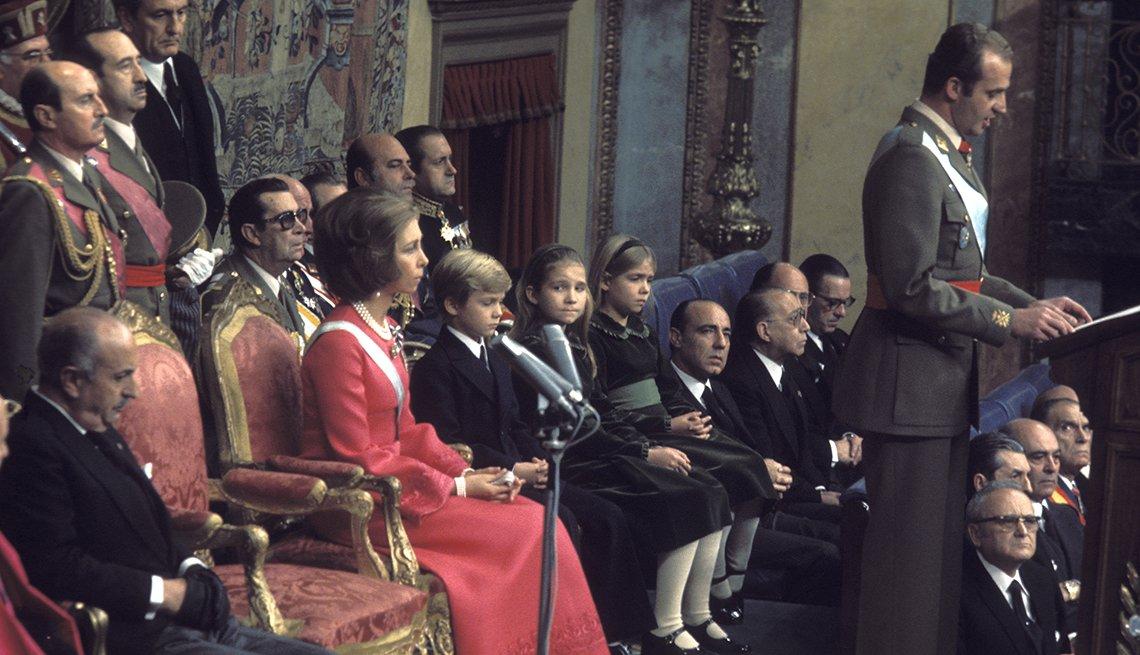 Foto de la coronación del rey Juan Carlos, mientras el da un discurso y la reina Sofia y sus hijos sentados detrás de él, al lado de altos oficiales del gobierno.