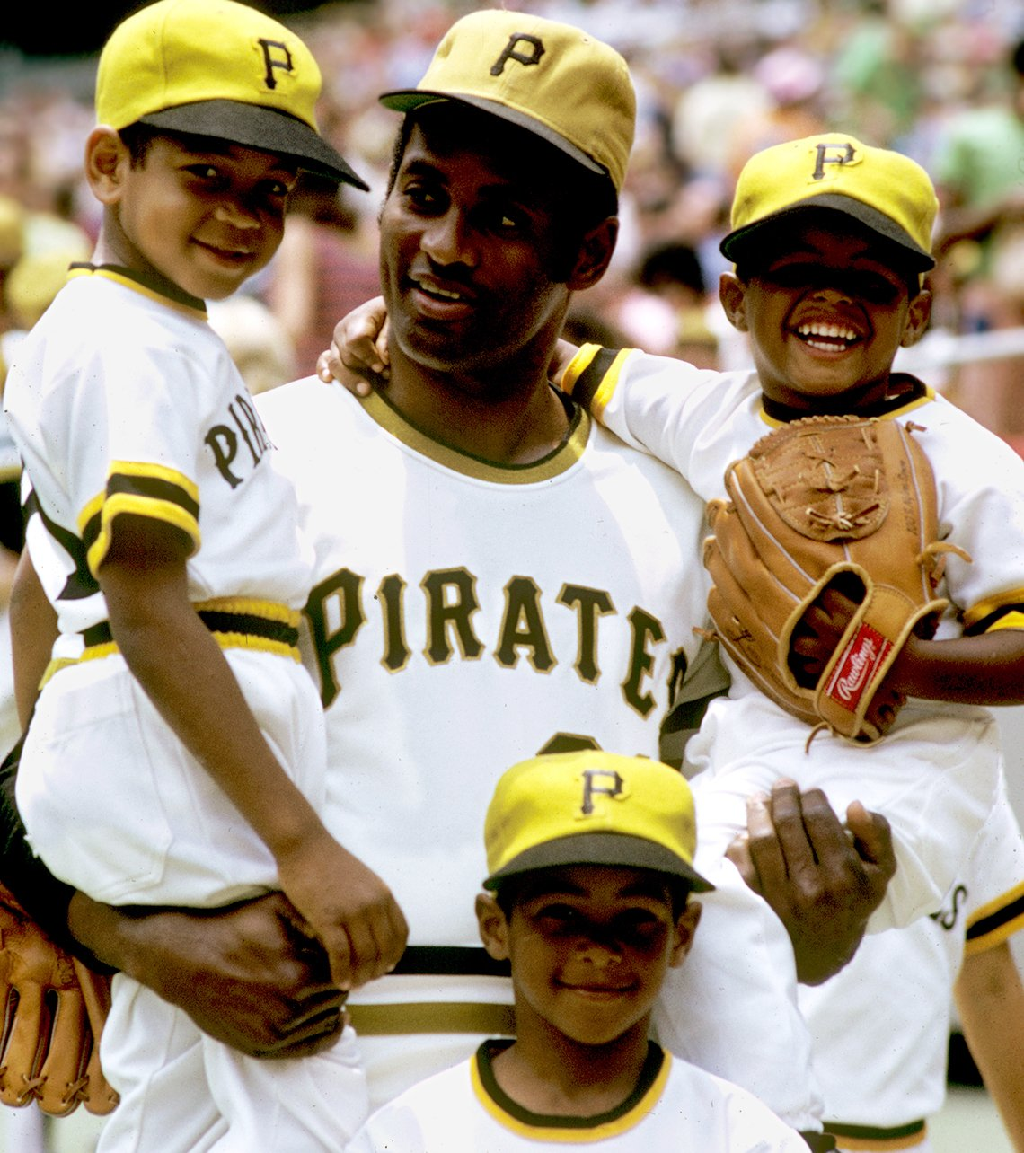 Pittsburgh Pirates Roberto Clemente stands in front of his father and brothers