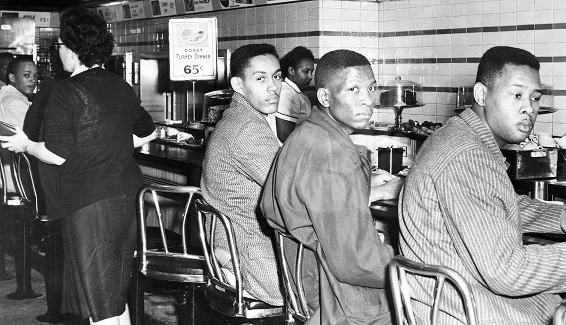three men sitting at a lunch counter