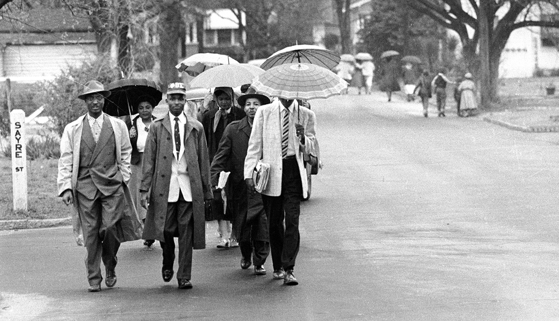 group of men holding umbrellas walking down a street during a bus boycott