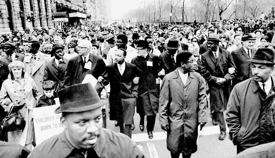 martin luther king marches, arms locked, in protest of the vietnam war