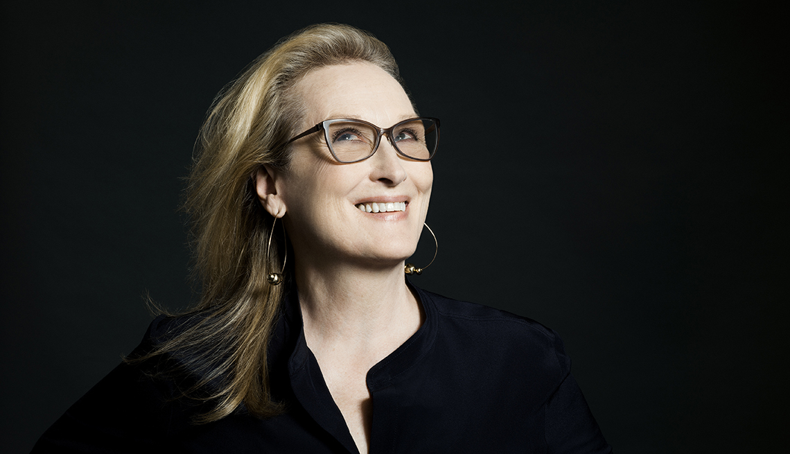 woman with blonde hair and glasses against a black background