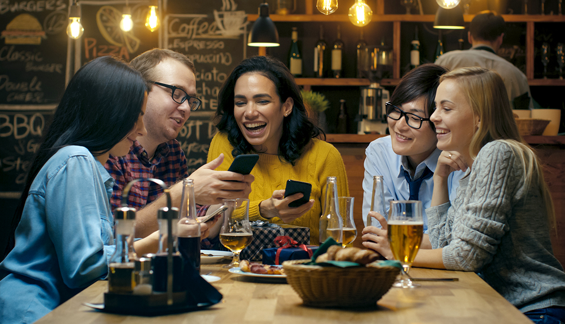 group of younger people in a bar, laughing and looking at phones
