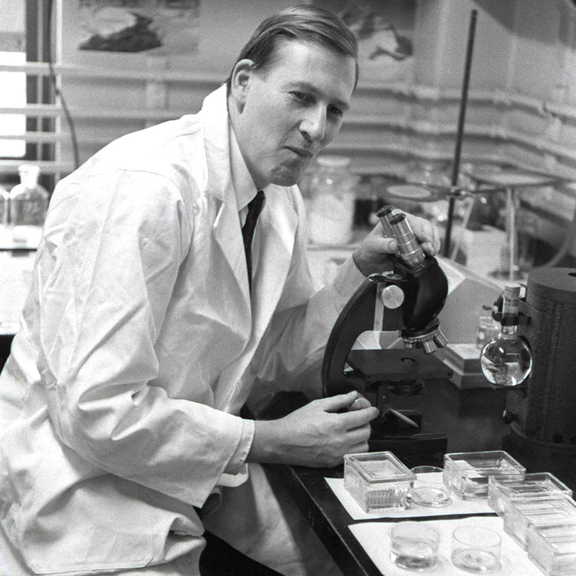 Roger Bannister using a microscope