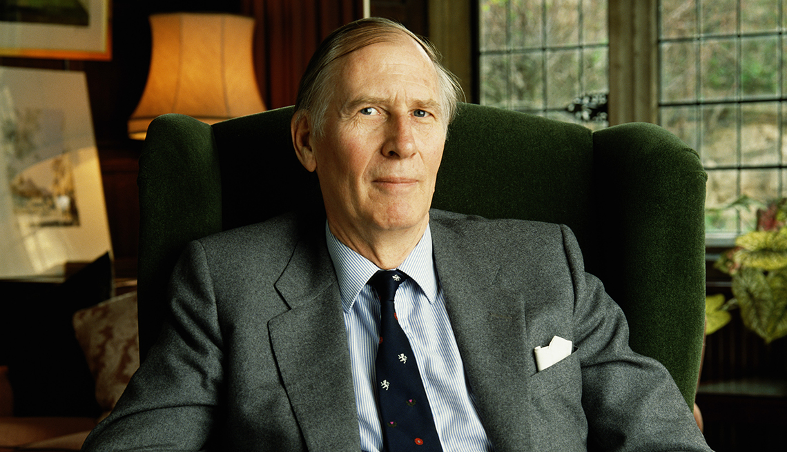 Roger Bannister sitting in upholstered chair, wearing suit