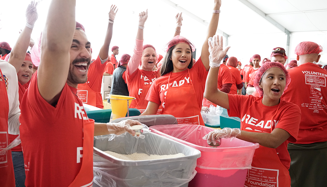 Voluntarios de AARP en un evento para empacar alimentos.