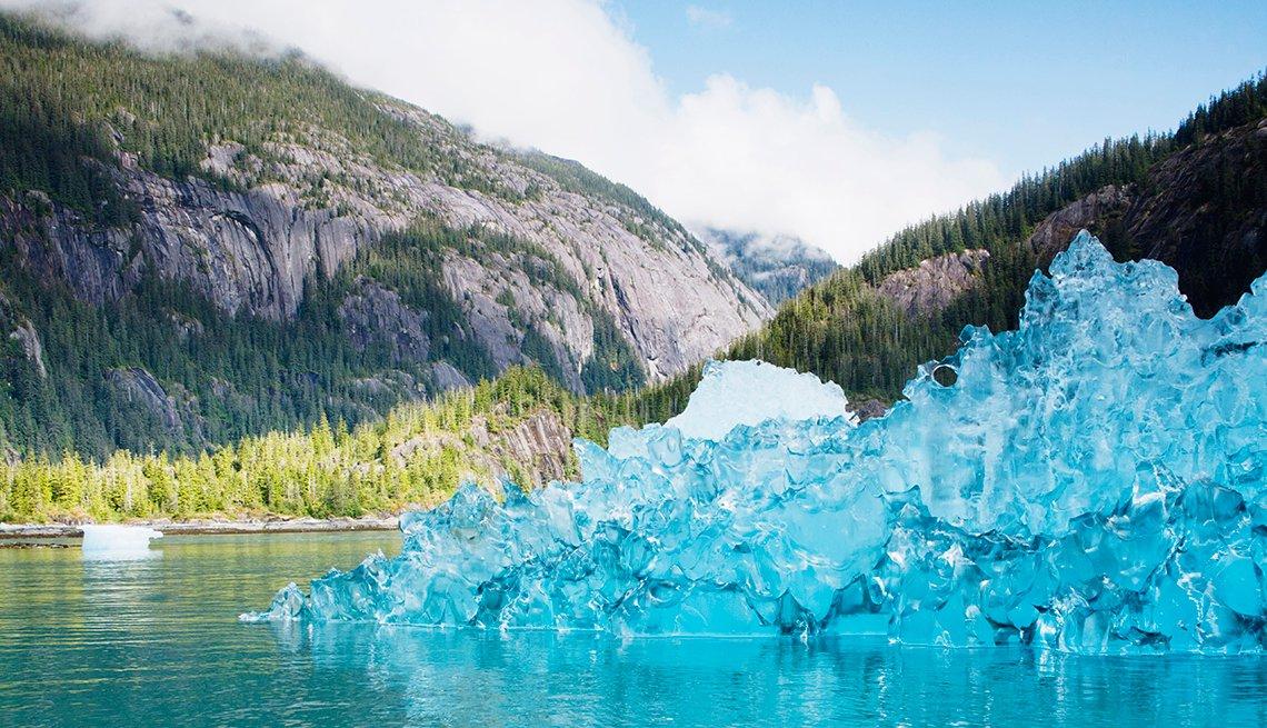 En Alaska, hielo azul apilado en el agua con montañas en el fondo.
