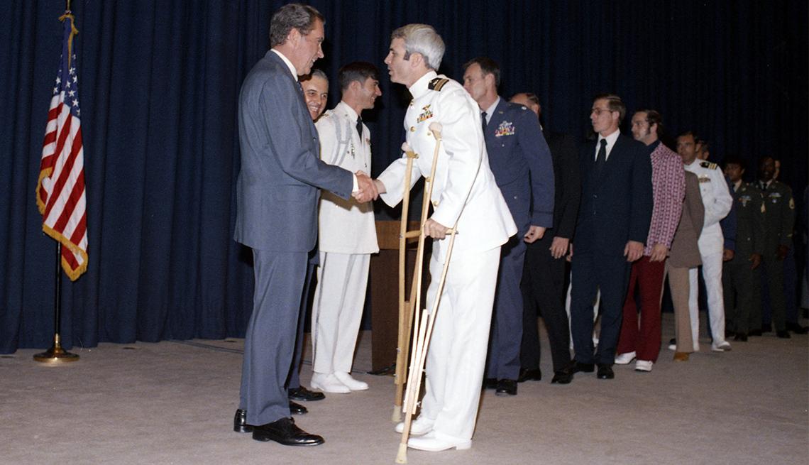 En una recepción antes de la cena, el presidente de los Estados Unidos Richard Nixon (1913-1994) estrecha la mano y saluda al ex prisionero de guerra norvietnamita (y futuro senador de EE. UU.) Capitán John McCain en 1973.
