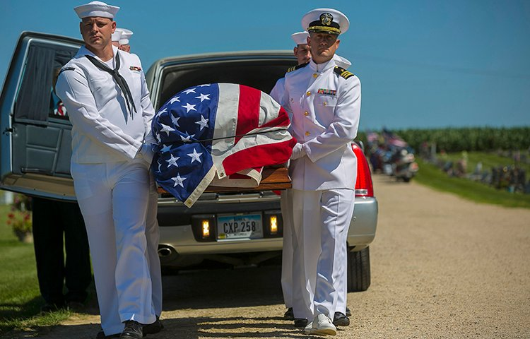 Sailors remove a casket from a hearse