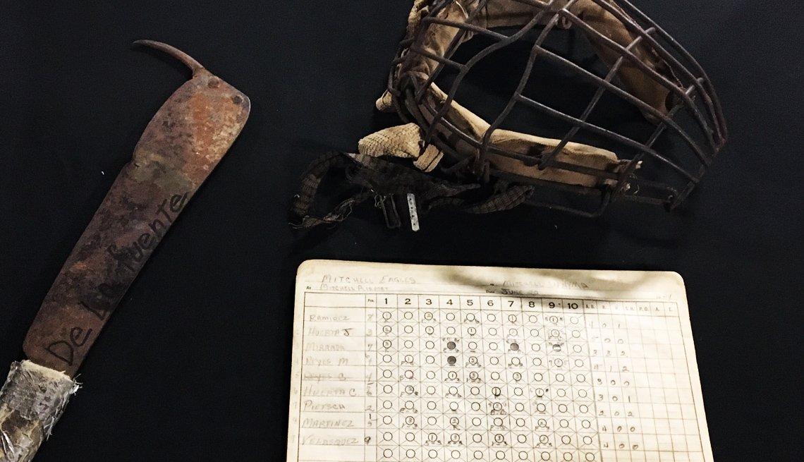 Careta de béisbol y una libreta de anotaciones junto a una herramienta de labranza.
