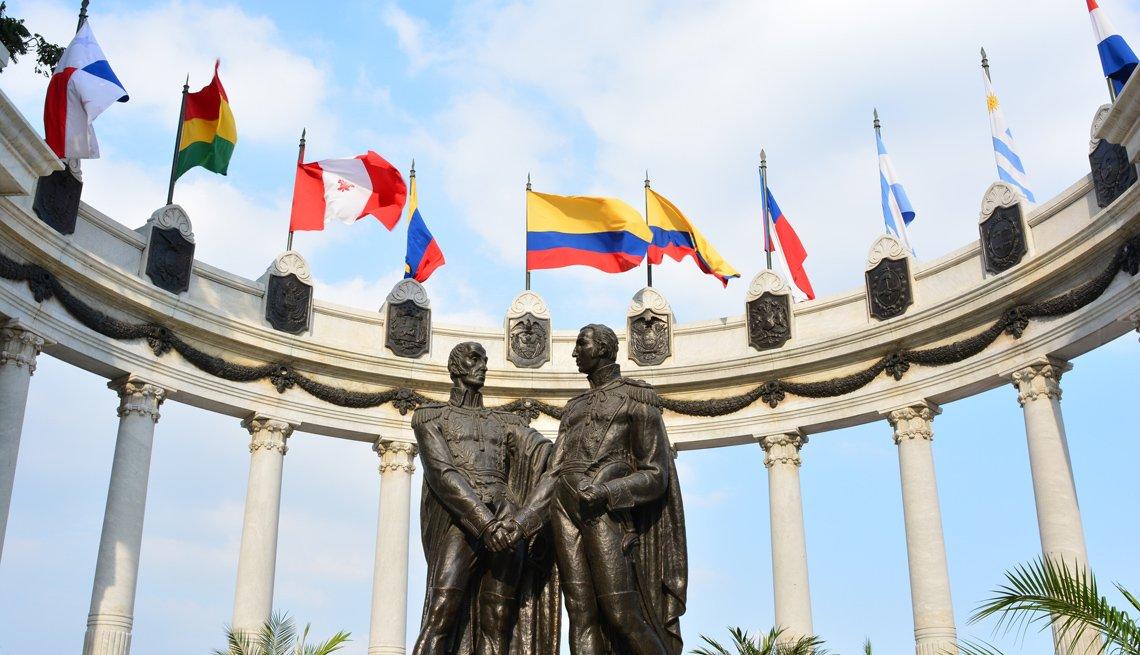 Banderas ondean junto a la estatua de Simón Bolívar y San Martín de los Andes en Guayaquil, Ecuador.