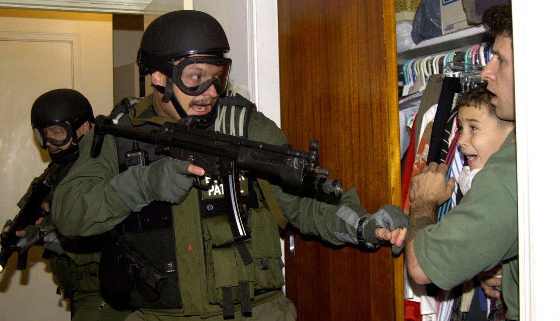 Militar armado apunta su arma a un niño y a un hombre que lo tiene en sus brazos.
