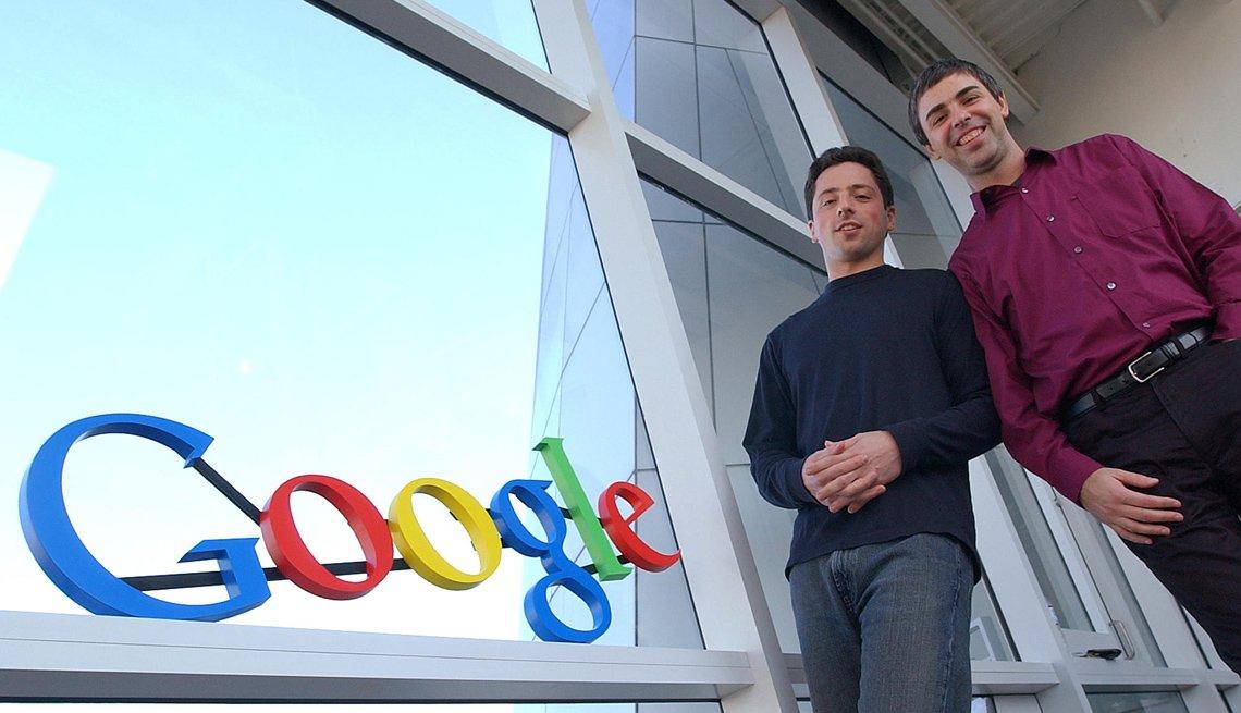 Dos hombres posan frente al logo del buscador Google