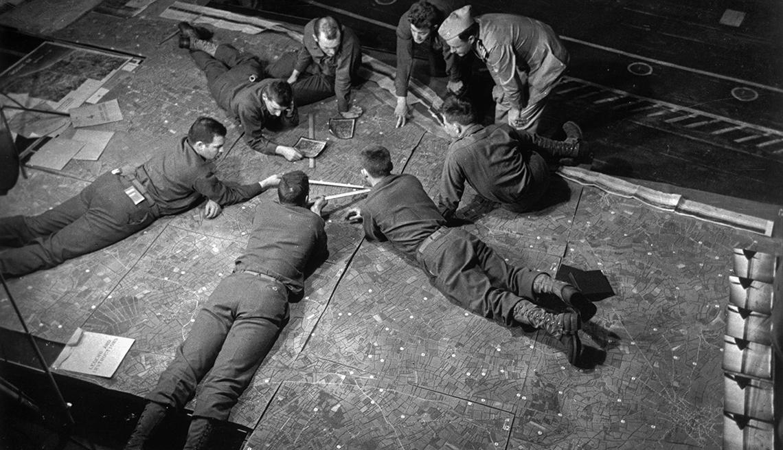 item 2 of Gallery image - Las tropas estadounidenses en un barco de transporte de la Guardia Costera repasan los detalles de los desembarques del Día D.