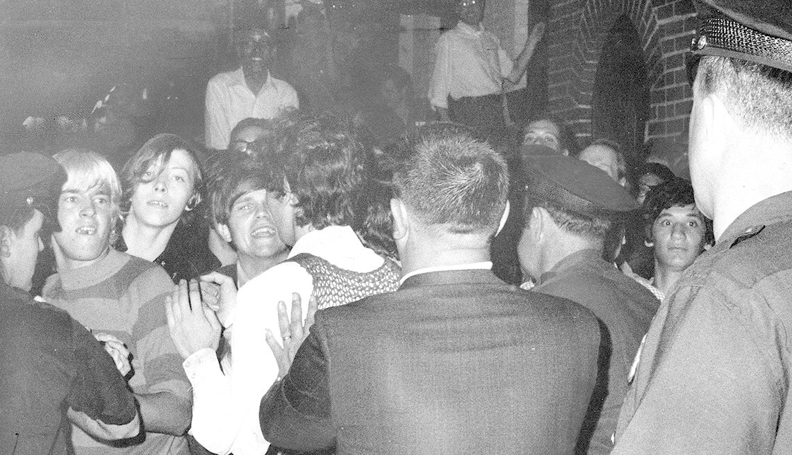 item 1, Gallery image. The crowd attempts to impede police during a raid on the Stonewall Inn in Greenwich Village.