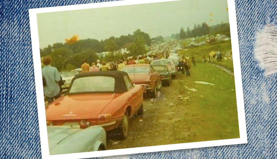 a long line of abandoned cars stopped in the field leading up to Woodstock, with people walking past them towards the festival barely visible in the distance