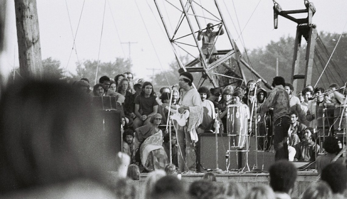 Jimi Hendrix and band onstage at Woodstock from the point of view of the crowd, with a partially obstructed view of the back of people's heads